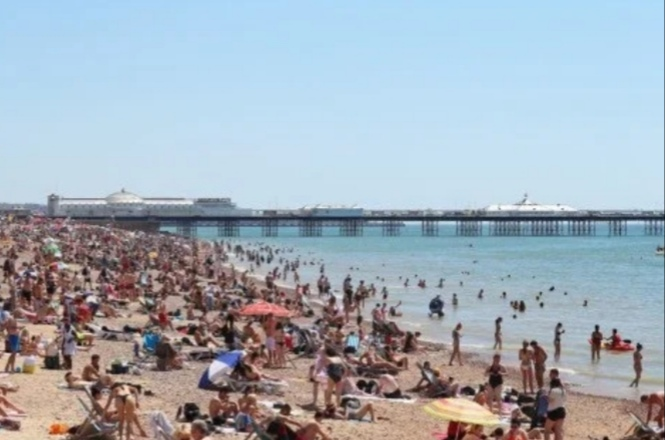People enjoying the warm weather at the Brighton Beaches of UK. This Friday may be the hottest weather of the year for UK