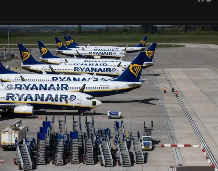 Three people walk on the running among parked and temporarily at Stansted airport outside London