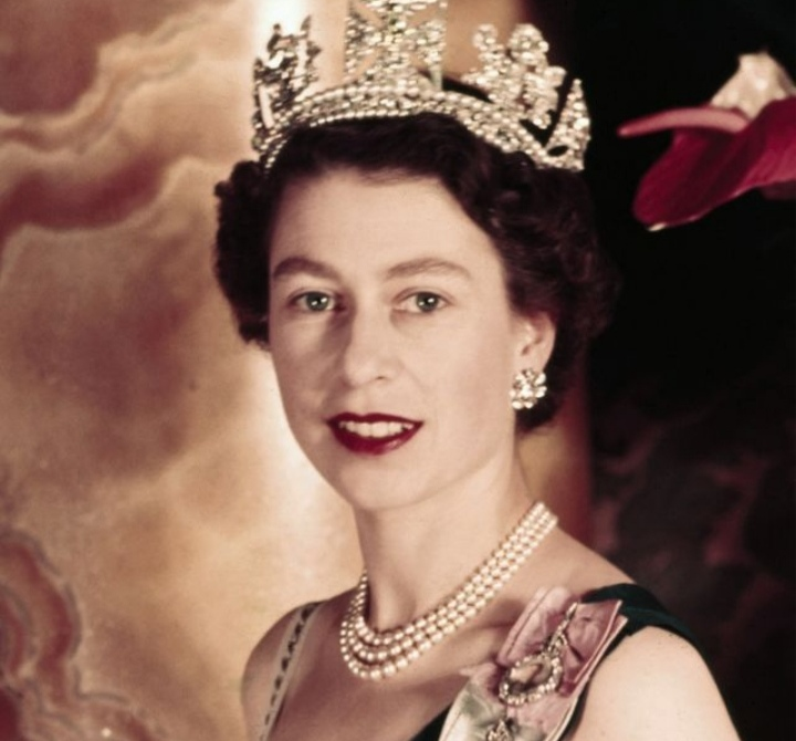 Queen Elizabeth ll in her early days. She is with her crown with a cute smiling.
