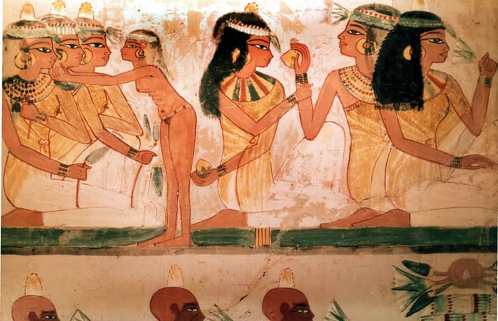 A detail of a painting from the tomb of Nakht depicting three ladies at a feast. They wear perfumed cones in their hair and elaborate necklaces.
