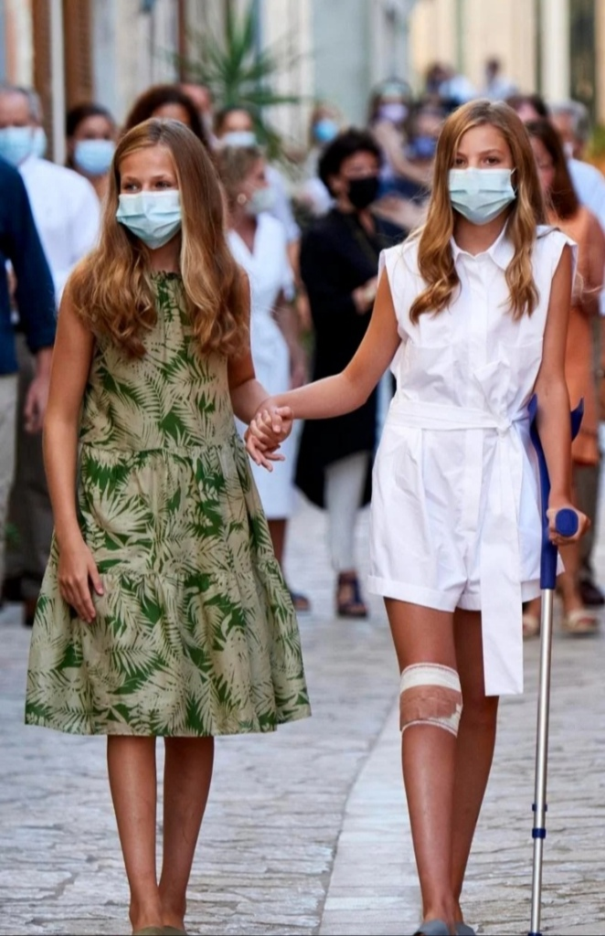 Princess Leonor gave her sister Infanta Sofia a wormly helping hand. And a crowds wearing face masks watched on as the Spanish royal greeted the local authorities who gave them the tour. Image © Getty Images